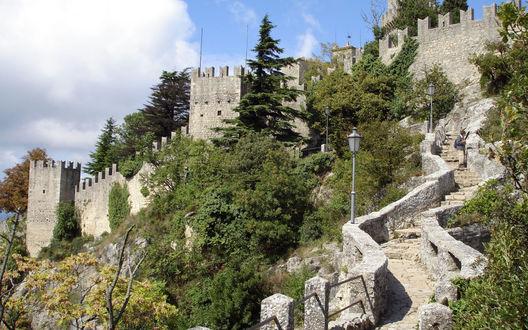 Обои Крутая каменная лестница, поднимающаяся к старой крепости среди деревьев