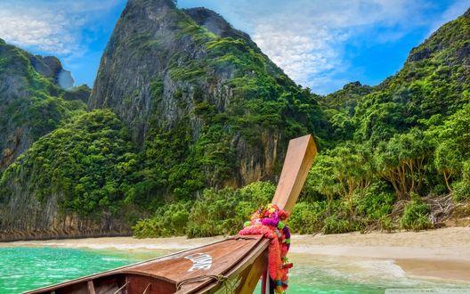 Обои Деревянная прогулочная лодка с яркими украшениями на носу на фоне бирюзового тропического моря и гор, поросших яркой зеленью