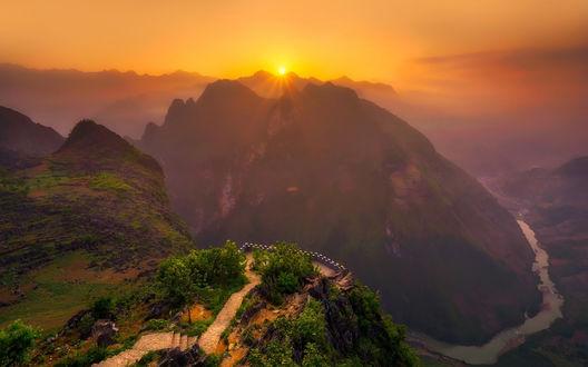 Обои Обзорная площадка в горах Вьетнама на фоне слепящего из-за вершин солнца