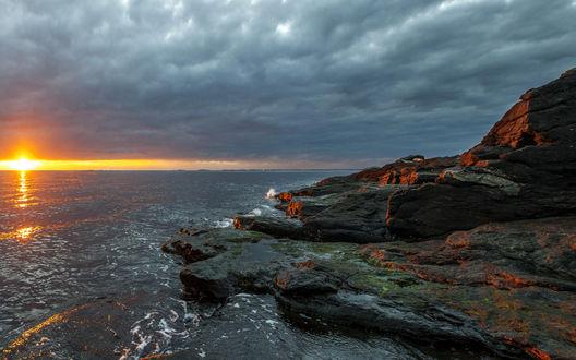 Обои Лучи заходящего солнца отражаются в сером море и на темных камнях берега, сверху плотные тучи