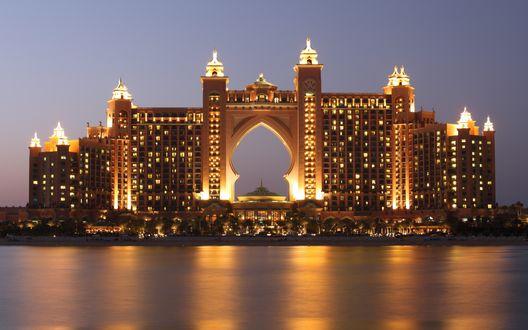 Обои Отель Атлантис на искусственном острове в Дубаях, ОАЭ на фоне моря при ярком вечернем освещении