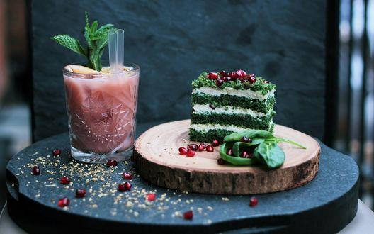 Обои Розовый коктейль с листочками мяты и рядом прикольное пирожное из зелени, посыпанное зернышками граната на деревянном подносе