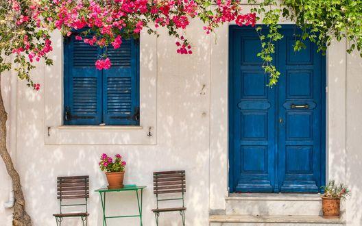 Обои Греческий дом с синей дверью и окном, столиком и стульями, стоящими возле, деревом, цветущим по крыше дома