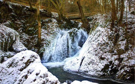 Обои Мостик над небольшим водопадом и заснеженным оврагом, поросшим деревьями, на дне которого течет узкий поток