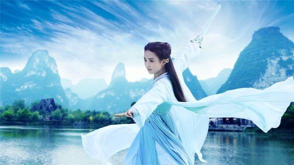 Обои Девушка с мечом на фоне горного пейзажа