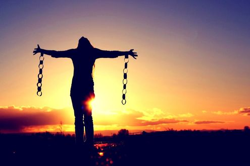 Обои Девушка с с разорванными оковами на раскинутых руках подняла голову к небу символизируя свободу