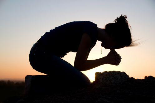 Обои Девушка стоит на коленях, приклонив голову к земле, сложив руки молится