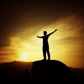 Обои Парень стоит на камне раскинув руки на фоне рассветного неба