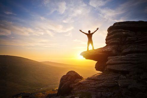 Обои Парень широко раскинув руки стоит на выступе скалы встречая рассвет в лучах солнца