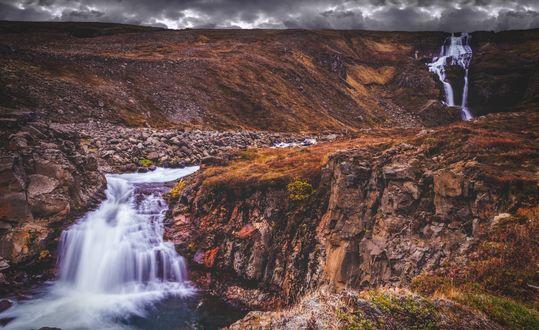 Обои Каскады водопадов, спадающих по широких каменных уступах рыжеватого цвета, вдали виднеются темно-серые тучи