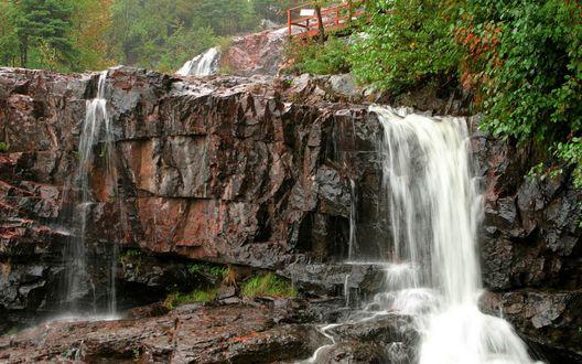 Обои Водопад спадает с гранитного каменного уступа, над ним сверху небольшой мостик