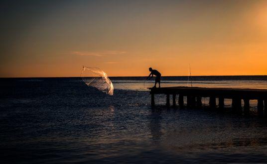 Обои Мужчина на пирсе проверяет рыбацкую сеть на фоне рассветного неба