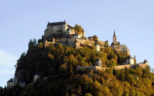 Обои Красивый старинный замок на вершине холма на фоне светло-голубого неба