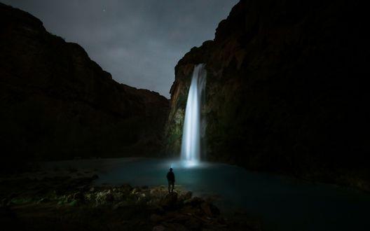 Обои Мужчина стоит ночью перед водопадом, подсвеченным луной