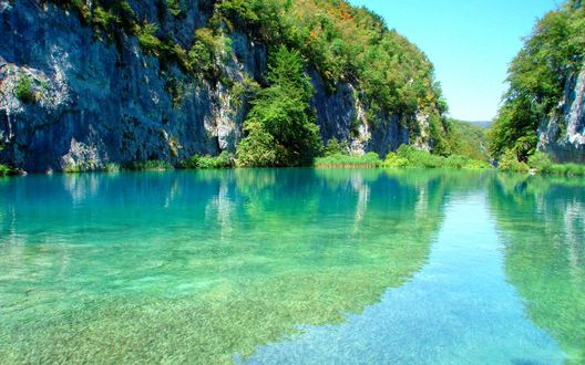 Обои Озеро в национальном парке Плитвицкие озера, Хорватия, с прозрачной водой, освещенное солнцем, на фоне горы, поросшей лесом
