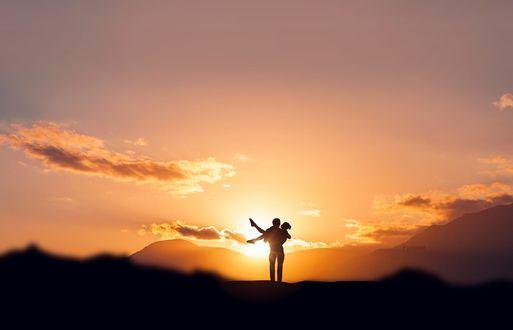 Обои Парень держит девушку на руках, стоя на фоне солнца, фотограф Stijn Dijkstra