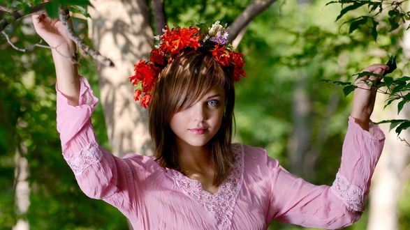 Обои Русоволосая девушка в розовой блузке и венке из красных цветом стоит среди деревьев, освещенная солнцем