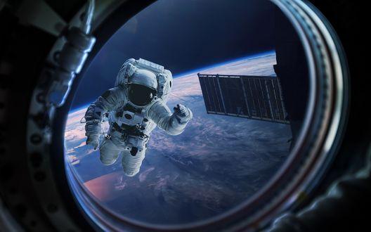 Обои Космонавт в открытом космосе машет рукой через иллюминатор на фоне земли