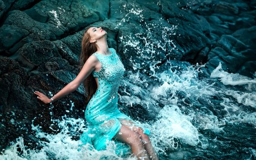 Обои Длинноволосая девушка в голубом платье сидит на камне на берегу моря, и ее захлестывает набегающая волна