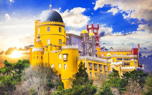 Обои Дворец Pena Palace, Португалия стоит на скале в лучах заката на фоне ярко-голубого неба с белыми тучками
