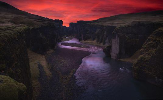 Обои Извилистая речка течет среди горного массива на фоне ярко-красного закатного неба