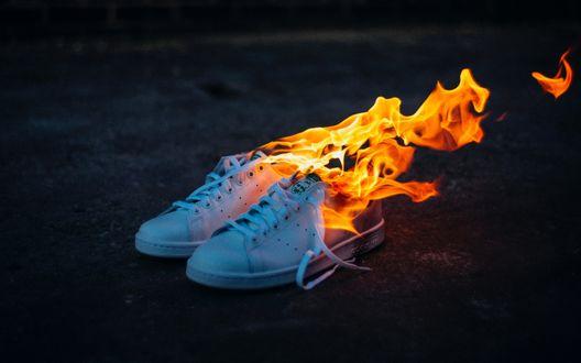 Обои Голубые кроссовки, объятые пламенем на темном размытом фоне
