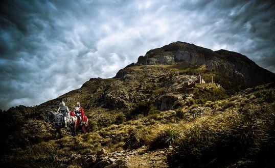 Обои Король и рыцарь стоят на горной дороге, позади них небольшая крепость на склоне горы и затянутое тучами небо