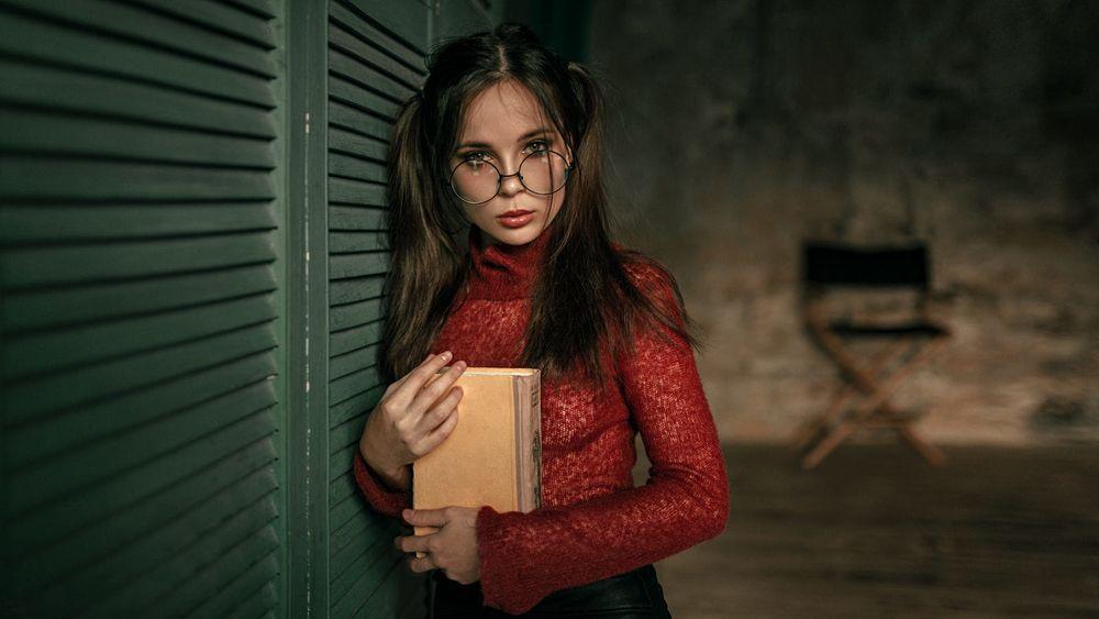Обои для рабочего стола Девушка в очках, с книгой в руках стоит у стены, фотограф Георгий Чернядьев