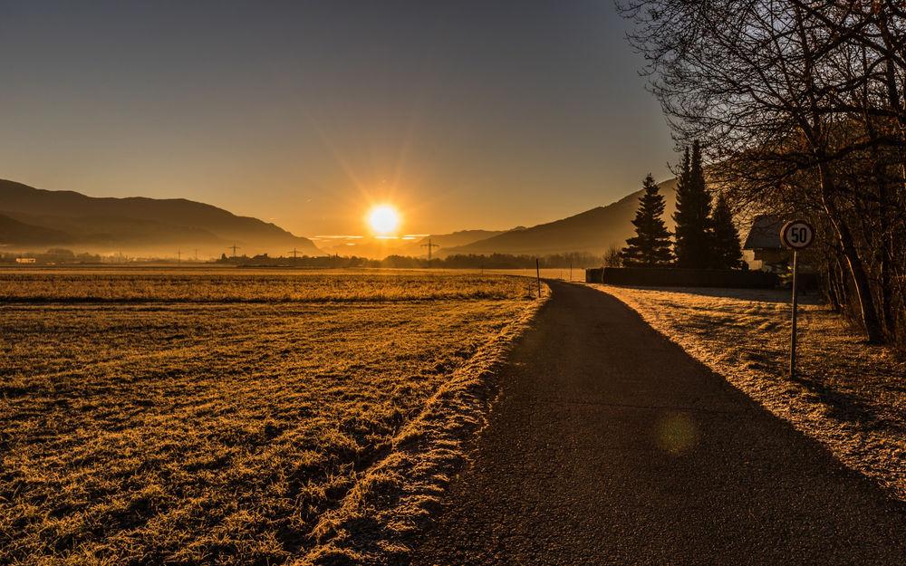 Обои для рабочего стола Восход над полями и дорогой, уходящей в горы
