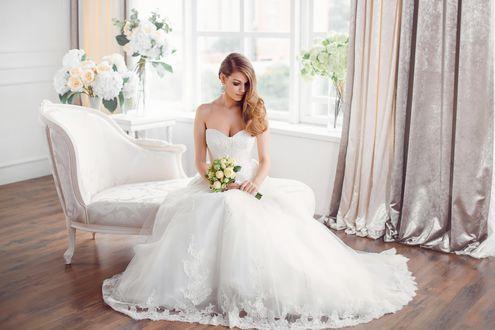 Обои Блондинка в свадебном платье с букетом сидит на кушетке в комнате