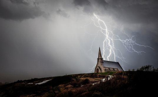 Обои Здание церкви в отдалении на холме, а над ней серое грозовое небо и разряд молнии, пересекающей небо