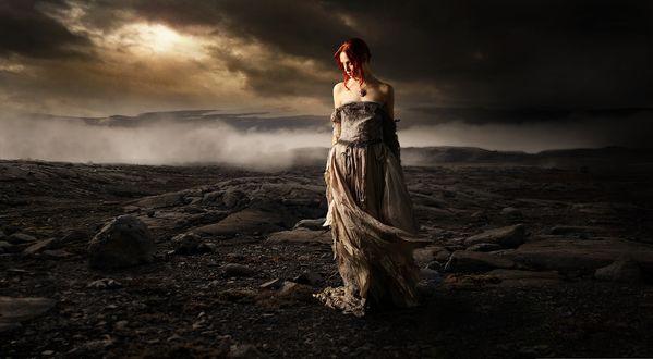 Обои Рыжеволосая девушка стоит на пустоши, а позади нее сгущается туман и небо заволакивает темная туча