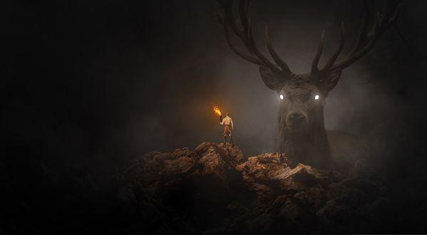 Обои Мужчина-охотник стоит с факелом на вершине горы, а перед ним из тумана появляется гигантская голова оленя со светящимися глазами