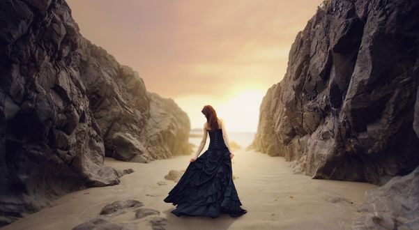 Обои Девушка в синем вечернем платье и с длинными рыжими волосами идет по проходу между скалами