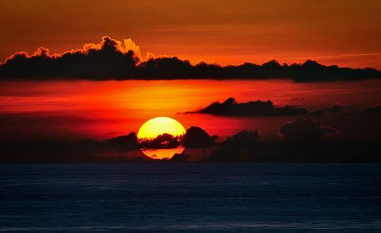 Обои Закат солнца, опускающегося в море, в черно-красных тонах