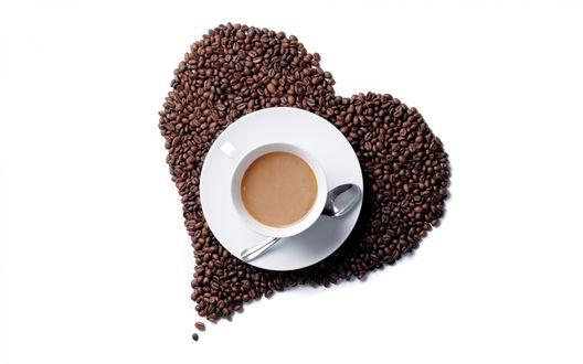 Обои Чашка кофе стоит среди кофейных зерен, насыпанных в форму сердечка