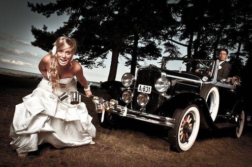 Обои Светловолосая улыбающаяся невеста в белом платье тащит свадебную машину со своим женихом