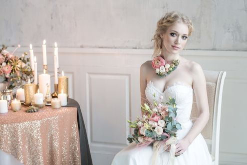 Обои Невеста в свадебном платье, с букетом, сидит у стола с горящими свечами и цветами