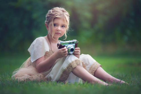 Обои Милая девочка с фотоаппартаом в руках сидит на траве, by Julia Altork
