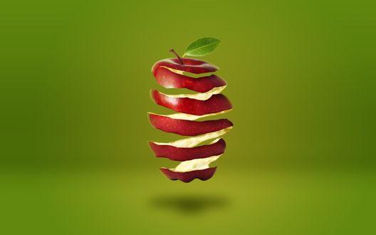 Обои Нарезанное спиралью красное яблоко на размытом зеленом фоне