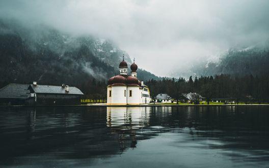 Обои Церковь стоит на берегу темного озера в небольшом городке, на заднем плане туман и тучи затягивают заснеженные горы и лес