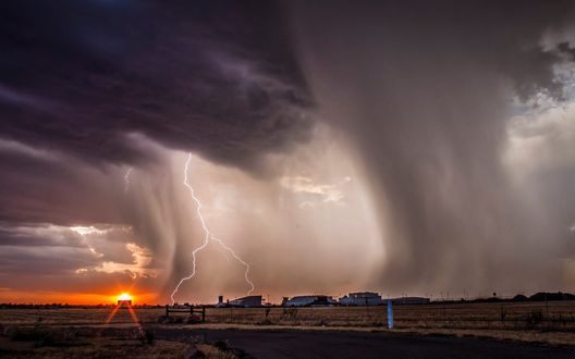 Обои Грозовой фронт с молниями над фермой на равнине на фоне заходящего солнца