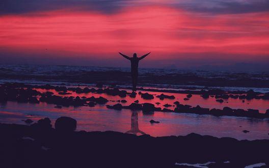 Обои Силуэт мужчины с раскинутыми руками, стоящего на берегу моря на фоне красного закатного неба