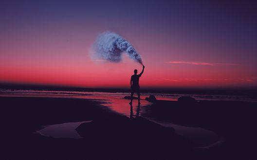 Обои Мужчина стоит на берегу моря с зажженной дымовой шашкой на фоне красного закатного неба
