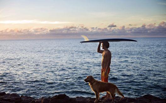 Обои Мужчина-серфер стоит на берегу моря на фоне заката, у его ног собака