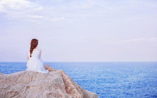 Обои Рыжеволосая девушка, сидящая к нам спиной на горе, на фоне морского пейзажа