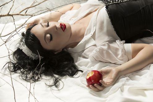 Обои Темноволосая девушка в образе Белоснежки с закрытыми глазами держит в руке надкусанное яблоко