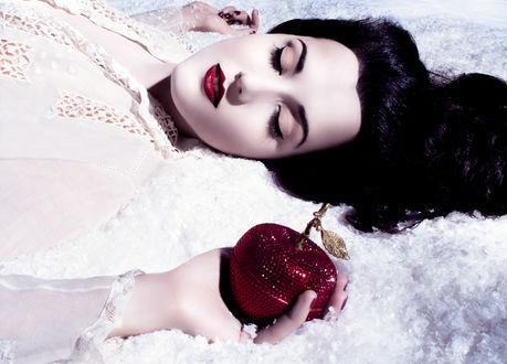 Обои Девушка в образе Белоснежки лежит на снегу держа в руке яблоко