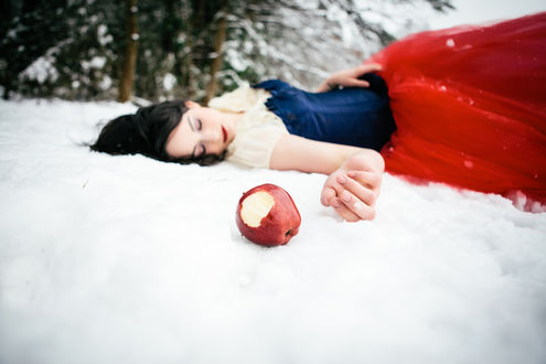 Обои Девушка в образе Белоснежки лежит на снегу у леса, рядом с ней лежит надкусанное яблоко