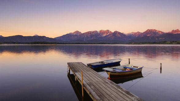 Обои Причаленные лодки на озере, на горизонте виднеются горы